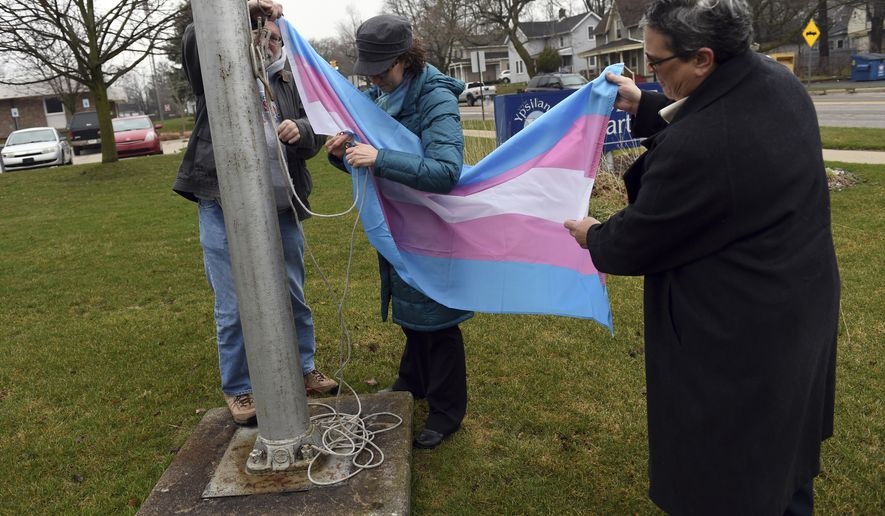From left, Ypsilanti City Council member Pete Murdock, Mayor Amanda Edmonds and City Council member Beth Bashert secure a transgender pride flag to the pole as they raise it during a ceremony for International Transgender Day of Visibility outside the Ypsilanti Police Department, in Ypsilanti, Mich., on Friday, March 31, 2017. (Melanie Maxwell/The Ann Arbor News via AP)