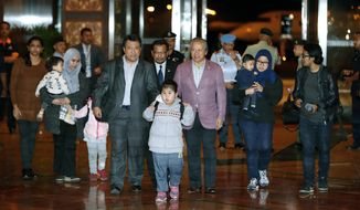 Malaysians who were stranded in Pyongyang walk with Malaysia's Foreign minister Anifah Aman, center right, after arriving at Kuala Lumpur International airport in Sepang, Malaysia, Friday, March 31, 2017. Malaysia said Thursday it has agreed to release the body of Kim Jong Nam to North Korea in exchange for the return of nine Malaysians held in the North's capital. (AP Photo/Vincent Thian)