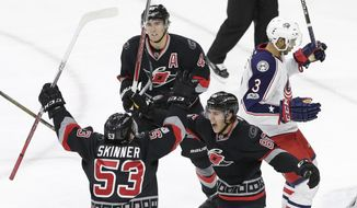 Carolina Hurricanes' Teuvo Teravainen (86), of Finland, celebrates with Jeff Skinner (53) and Victor Rask, top, of Sweden, following Skinner's goal while Columbus Blue Jackets' Seth Jones (3) skates away during the third period of an NHL hockey game in Raleigh, N.C., Thursday, March 30, 2017. Carolina won 2-1 in overtime. (AP Photo/Gerry Broome)