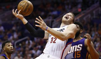 Los Angeles Clippers' Blake Griffin (32) tries to shoot over Phoenix Suns' Alan Williams (15) as Suns' Ronnie Price, left, looks on during the first half of an NBA basketball game Thursday, March 30, 2017, in Phoenix. (AP Photo/Ross D. Franklin)