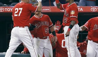 Los Angeles Angels' Mike Trout, left, celebrates with Martin Maldonado, right, after Trout scored on a two-run single by C.J. Cron against the Los Angeles Dodgers during the seventh inning of an exhibition baseball game in Anaheim, Calif., Thursday, March 30, 2017. (AP Photo/Alex Gallardo)