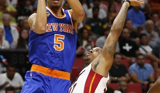 New York Knicks' Courtney Lee (5) shoots the ball over Miami Heat's Rodney McGruder (17) during the first half of an NBA basketball game, Friday, March 31, 2017, in Miami. (AP Photo/Joel Auerbach)
