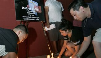 FILE - In this Sunday, April 22, 2012 file photo, people place their candles at the bottom of a large poster of missing six-year-old Isabel Celis during a candlelight vigil near a police command post in Tucson, Ariz., Tucson police Chief Chris Magnus says remains found in a remote area in Pima County about a month ago are those of six-year-old Isabel Celis, who went missing from her family home nearly five years ago. Magnus said Friday, March 31, 2017, that an independent lab identified the remains as those of Celis. He said an investigation is ongoing but would not say whether there were any new suspects. (AP Photo/Benjie Sanders/Arizona Daily Star)