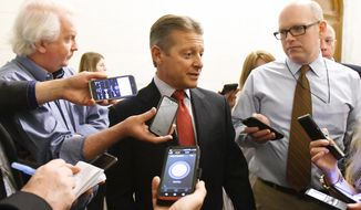 Sen. Patrick Gallivan, R-Elma, center, talks with reporters as legislative members work on the state budget at the state Capitol on Friday, March 31, 2017, in Albany, N.Y. (AP Photo/Hans Pennink)