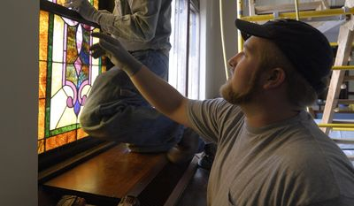 ADVANCE FOR THE WEEKEND OF APRIL 1-2 AND THEREAFTER - In a March 22, 2017 photo, Kenne Kruse and Jason Kruse of Kruse Stained Glass of Hartington works to install windows at St. Paul's Lutheran Church in Norfolk, Neb. Kenny and Kristi Kruse started Kruse Stained Glass after a specialist hired to complete a local restoration project couldn't complete the job. (Jake Wragge/The Norfolk Daily News via AP)
