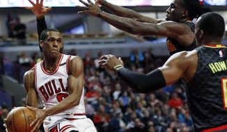 Chicago Bulls guard Rajon Rondo (9) looks to pass against Atlanta Hawks guard Dennis Schroder, forward Taurean Prince and center Dwight Howard during the first half of an NBA basketball game Saturday, April 1, 2017, in Chicago. (AP Photo/Nam Y. Huh)