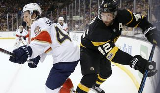 Boston Bruins' David Backes (42) and Florida Panthers' Michael Sgarbossa (48) battle in the corner during the second period of an NHL hockey game in Boston, Saturday, April 1, 2017. (AP Photo/Michael Dwyer)