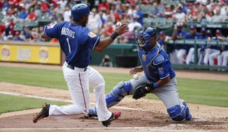Texas Rangers' Elvis Andrus (1) scores a run as Kansas City Royals catcher Salvador Perez (13) fails to control the ball at home during the second inning of an exhibition baseball game Saturday, April 1, 2017, in Arlington, Texas. (AP Photo/Michael Ainsworth)