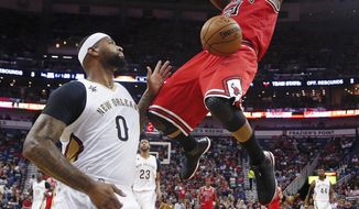 Chicago Bulls forward Jimmy Butler (21) slam-dunks over New Orleans Pelicans forward DeMarcus Cousins (0) in the first half of an NBA basketball game in New Orleans, Sunday, April 2, 2017. (AP Photo/Gerald Herbert)