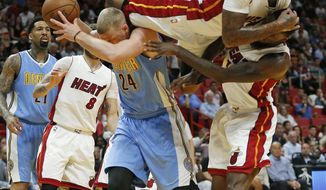 Miami Heat's James Johnson (16) falls over Denver Nuggets' Mason Plumlee (24) as he attempts to block a shot during the first half of an NBA basketball game, Sunday, April 2, 2017, in Miami. (AP Photo/Joel Auerbach)
