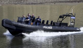 Police patrol the River Thames prior to the annual university Oxford-Cambridge boat race along the river , London, Sunday April 2, 2017.  Police have said the annual event will go ahead after a World War II era bomb was safely removed from the shallows of the river near to the start of the race at Putney Bridge in southwest London. (Andrew Matthews/PA Wire(/PA via AP)