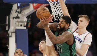 Boston Celtics' Amir Johnson, second from right, grabs a rebound in front of New York Knicks' Kristaps Porzingis, right, and Willy Hernangomez during the first half of the NBA basketball game, Sunday, April 2, 2017, in New York. (AP Photo/Seth Wenig)