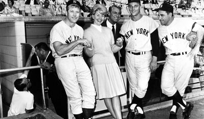 """FILE - In this July 12, 1962 file photo, actress Doris Day and actor Cary Grant, standing in the dugout, pose with New York Yankees players, from left, Mickey Mantle, Roger Maris and Yogi Berra before the Yankees-Dodgers game in Los Angeles. The players appeared in the movie """"A Touch of Mink"""" with Day and Grant. Film and recording star Day is marking her 95th birthday Monday, April 3, 2017, with a social media campaign to highlight her love of animals. (AP Photo/Ed Widdis, File)"""