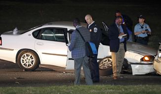 Investigators with Metropolitan Police Department examine the scene after a pursuit Sunday, April 2, 2017, in Washington. According to Capt. David Sledge with the Metropolitan Police Department, officers arrested a man after the pursuit and rescued a girl who was reported missing from a Charlotte, N.C., home. (AP Photo/Alex Brandon)