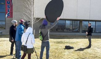 "Actor Manny Crespin, right, appears during the filming of ""Black Coffee"" on the campus of Colorado State University-Pueblo in Pueblo, Colo., on March 7, 2017. Film director Josh Munson, left, and CSU-Pueblo philosophy professor Andrew Corsa worked with students to make a philosophy-based film. (John Jaques/The Pueblo Chieftain via AP)"