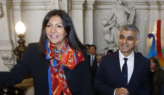 Mayor of Paris, Anne Hidalgo, left, welcomes her London counterpart, Sadiq Khan, before their meeting with the mayor of Seoul at the City Hall of Paris, France, Wednesday, March 29, 2017. The mayors of Paris, London and Seoul are creating a system to grade vehicles based on their emissions in real-life conditions, after growing uncertainty about automakers efforts to skirt rules intended to limit pollutants. (AP Photo/Francois Mori)