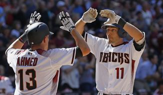 Arizona Diamondbacks' A.J. Pollock (11) celebrates his two-run home run against the San Francisco Giants with Nick Ahmed (13) during the sixth inning of an Opening Day baseball game Sunday, April 2, 2017, in Phoenix. (AP Photo/Ross D. Franklin)
