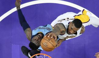 Memphis Grizzlies forward James Ennis III, left, tries to block the shot of Los Angeles Lakers forward Thomas Robinson during the first half of an NBA basketball game, Sunday, April 2, 2017, in Los Angeles. (AP Photo/Mark J. Terrill)