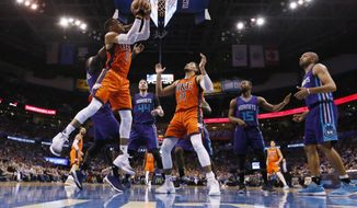 Oklahoma City Thunder guard Russell Westbrook, left, drives to the basket during the second quarter of the team's NBA basketball game against the Charlotte Hornets in Oklahoma City, Sunday, April 2, 2017. (AP Photo/Sue Ogrocki)