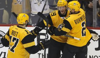Pittsburgh Penguins' Jake Guentzel (59) celebrates his goal with Chad Ruhwedel (2) and Bryan Rust (17) in the first period of an NHL hockey game against the Carolina Hurricanes in Pittsburgh, Sunday, April 2, 2017. (AP Photo/Gene J. Puskar)
