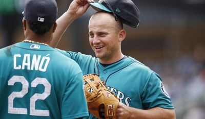 Seattle Mariners' Kyle Seager, right, talks with Robinson Cano (22) on the field during the second inning of a spring training baseball game against the Colorado Rockies, Saturday, April 1, 2017, in Scottsdale, Ariz. (AP Photo/Ross D. Franklin)