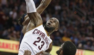 Cleveland Cavaliers' LeBron James (23) dunks against Indiana Pacers' Paul George (13) during the first half of an NBA basketball game, Sunday, April 2, 2017, in Cleveland. (AP Photo/Tony Dejak)