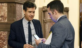 Sen. Brad Hoylman, D-New York, left, talks with staff counsel Burton Phillips as legislative leaders work on the state budget at the state Capitol, Sunday, April 2, 2017, in Albany, N.Y. (AP Photo/Hans Pennink)