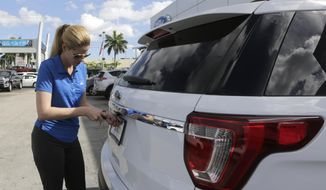 In this Tuesday, Jan. 17, 2017, photo, Ford sales consultant Yanaisis Milian removes the dealer tag on a sold 2017 Ford Explorer at an auto dealership in Hialeah, Fla. Automakers are reporting financial results Monday, April 3, 2017. (AP Photo/Alan Diaz)