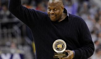 FILE - In this March 9, 2013, file photo, former NBA and Georgetown basketball player Patrick Ewing acknowledges the crowd after he was recognized with an award during a ceremony at the NCAA college basketball game between Georgetown and Syracuse, in Washington. A person with direct knowledge of the situation says former Georgetown star Patrick Ewing has been hired to coach the school's basketball team, more than two decades after he led the Hoyas to their only national championship as a player. The person spoke to The Associated Press on condition of anonymity because the school has not announced the hire.. (AP Photo/Nick Wass, File)