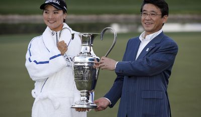 ANA CEO Shinya Katanozaka, right, holds the trophy with So Yeon Ryu, left, after Ryu won the LPGA Tour's ANA Inspiration golf tournament at Mission Hills Country Club in Rancho Mirage, Calif., Sunday, April 2, 2017. (AP Photo/Alex Gallardo)