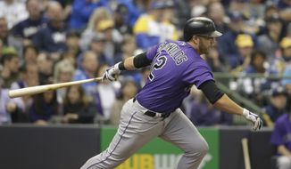 Colorado Rockies' Mark Reynolds hits a run-scoring single against the Milwaukee Brewers during the fourth inning of an opening day baseball game Monday, April 3, 2017, in Milwaukee. (AP Photo/Jeffrey Phelps)