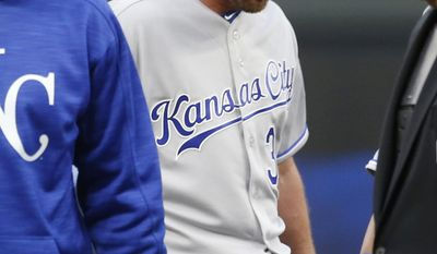 Kansas City Royals pitcher Travis Wood gets a visit to the mound during a tough seven inning against the Minnesota Twins in relief during a baseball game Monday, April 3, 2017 in Minneapolis. The Twins won 7-1. Wood gave up two bases loaded walks in the inning. (AP Photo/Jim Mone)