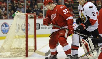 Detroit Red Wings right wing Evgeny Svechnikov (37), of Russia, tries to control the puck against Ottawa Senators defenseman Dion Phaneuf (2) during the second period of an NHL hockey game, Monday, April 3, 2017, in Detroit. (AP Photo/Jose Juarez)