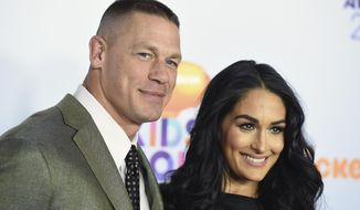 FILE - In this Saturday, March 11, 2017, file photo, John Cena, left, and Nikki Bella arrive at the Kids' Choice Awards at the Galen Center in Los Angeles. Cena and Bella finished off their opponents at WrestleMania and then decided to take on what could be their biggest challenge yet: Marriage. Cena got down on one knee after the pair defeated The Miz and Marse in a tag team match Sunday, April 2, at WrestleMania 33. (Photo by Jordan Strauss/Invision/AP, File)