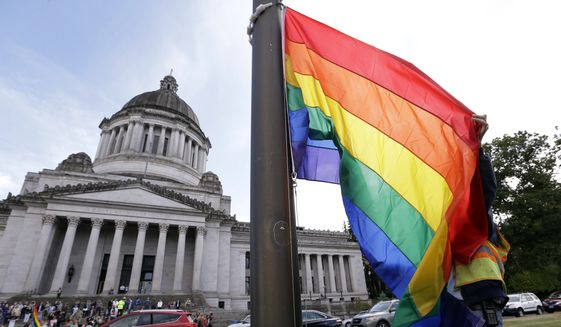 A state worker unfurls a rainbow flag in front of the Washington state Capitol to prepare it to be raised and then lowered to half-staff to mark last weekend's mass shooting at a central Florida nightclub, Wednesday, June 15, 2016, in Olympia, Wash. Gov. Jay Inslee and members from the LGBT community later raised the flag in honor of Gay Pride month, before it was lowered. A gunman wielding an assault-type rifle and a handgun opened fire inside Pulse, a crowded gay nightclub in Orlando, Florida, early Sunday, leaving at least 49 people dead in the worst mass shooting in modern U.S. history. (AP Photo/Elaine Thompson)