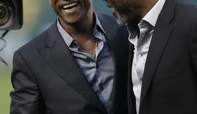 Former Oakland Athletic and Baseball Hall of Fame inductee Rickey Henderson, left, laughs with former Athletics pitcher Dave Stewart after a ceremony dedicating Rickey Henderson field prior to the baseball game against the Los Angeles Angels Monday, April 3, 2017, in Oakland, Calif. (AP Photo/Ben Margot)