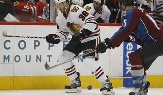 Chicago Blackhawks left wing Ryan Hartman, left, loses control of the puck as Colorado Avalanche defenseman Duncan Siemens defends in the second period of an NHL hockey game Tuesday, April 4, 2017, in Denver. (AP Photo/David Zalubowski)
