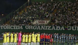 Players of Colombia's Atletico Nacional, left, and Brazil's Chapecoense, stand to listen the Brazilian national anthem, prior to their Recopa Sudamericana first leg final soccer match in Chapeco, Brazil, Tuesday, April 4, 2017. (AP Photo/Andre Penner)