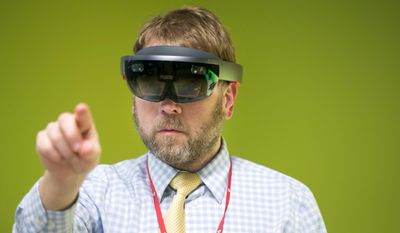 Brian Curtis demonstrates how to use a HoloLens self contained interaction computer prior to a groundbreaking ceremony for the future Dr. Edwin & Dorthy Balbach Davis Global Center for Advanced Interprofessional Learning at the University of Nebraska Medical Center Monday, April 3, 2017, in Omaha, Neb. (Brendan Sullivan/Omaha World-Herald via AP)