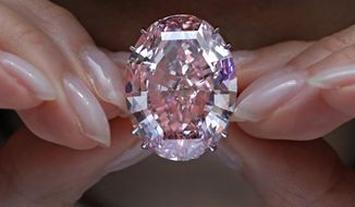 """In this Wednesday, March 29, 2017, file photo, the """"Pink Star"""" diamond, the most valuable cut diamond ever offered at auction, is displayed by a model at a Sotheby's auction room in Hong Kong. The stunning 59.6 carat diamond has sold for HK $553 million or US $71.2 million at a Sotheby's auction in Hong Kong, setting a record for any diamond or jewel. It's Also the highest price for any work ever sold at auction in Asia. (AP Photo/Vincent Yu, File)"""