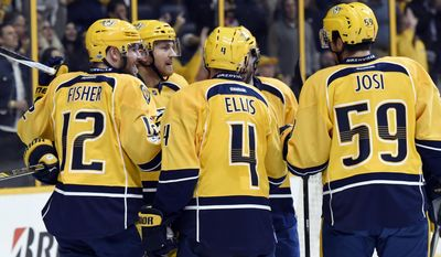 Nashville Predators center Mike Fisher (12) celebrates with Ryan Ellis (4) and Roman Josi (59), of Switzerland, after Fisher scored a goal against the New York Islanders during the second period of an NHL hockey game Tuesday, April 4, 2017, in Nashville, Tenn. (AP Photo/Mark Zaleski)