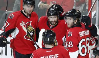 Ottawa Senators' Tom Pyatt (10) celebrates his goal with teammates Ben Harpur (67), Mike Hoffman (68) and Dion Phaneuf (2) during the second period of an NHL hockey game against the Detroit Red Wings, in Ottawa, Ontario, Tuesday, April 4, 2017. (Fred Chartrand/The Canadian Press via AP)