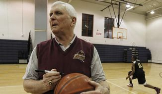 FILE - In this Wednesday, Feb. 2, 2011, file photo, Bob Hurley, head coach of the St. Anthony High School boys' basketball team, signs a game ball in Jersey City, N.J. In a half century at St. Anthony's, Hall of Fame basketball coach Bob Hurley has won on an almost unparalleled level in high school. But now the school that has been a haven to the poor seeking a Roman Catholic education could soon be closing its doors. (AP Photo/Julio Cortez, file) **FILE**