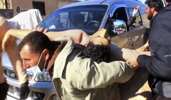 This frame grab from video provided on Tuesday April 4, 2017, by Qasioun News Agency, that is consistent with independent AP reporting, shows a Syrian man carrying a man on his back who has suffered from a suspected chemical attack, in the town of Khan Sheikhoun, northern Idlib province, Syria. The suspected chemical attack killed dozens of people on Tuesday, Syrian opposition activists said, describing the attack as among the worst in the country's six-year civil war. (Qasioun News Agency, via AP)