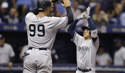 New York Yankees' Ronald Torreyes, right, high fives Aaron Judge after Torreyes hit a two-run home run off Tampa Bay Rays starting pitcher Jake Odorizzi during the third inning of a baseball game Tuesday, April 4, 2017, in St. Petersburg, Fla. (AP Photo/Chris O'Meara)
