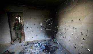 A soldier enters a bullet-riddled home, tagged with the initials CDG for the Gulf Cartel, and Z for Zetas, in Ciudad Victoria, in Mexico's state of Tamaulipas on Sept. 6, 2014. (Associated Press) **FILE**