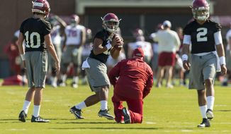 FILE - In this March 21, 2017, file photo, Alabama quarterbacks Mac Jones (10) Tua Tagovailoa (13) and Jalen Hurts (2) work with offensive coordinator Brian Daboll during a college football spring practice, in Tuscaloosa, Ala. As good as Alabama quarterback Jalen Hurts was as a freshman, he knows he has plenty to improve on this offseason. He's got a new offensive coordinator and two freshmen vying for the backup job. (Vasha Hunt/AL.com via AP)