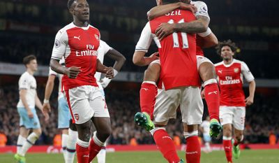 Arsenal's Theo Walcott, top right, celebrates his goal with Arsenal's Mesut Ozil, during the English Premier League soccer match between Arsenal and West Ham at the Emirates stadium in London, Wednesday, April 5, 2017.(AP Photo/Frank Augstein)