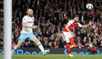 Arsenal's Olivier Giroud, right, shoots to score during the English Premier League soccer match between Arsenal and West Ham at the Emirates stadium in London, Wednesday, April 5, 2017.(AP Photo/Frank Augstein)