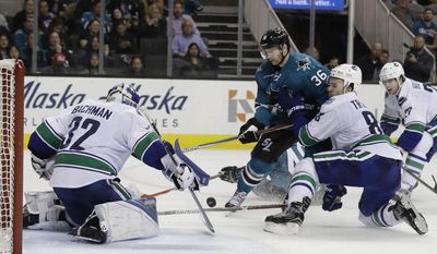 San Jose Sharks' Jannik Hansen, center, takes a shot on Vancouver Canucks goalie Richard Bachman (32) as Nikita Tryamkin, right, defends during the second period of an NHL hockey game Tuesday, April 4, 2017, in San Jose, Calif. (AP Photo/Marcio Jose Sanchez)
